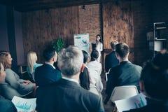 Audiência dos participantes à moda agradáveis do fórum que escutam para relatar a resultado da finança da exibição do gerente sup imagens de stock