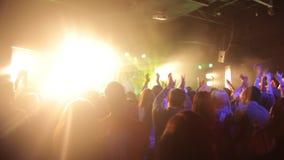 A audiência em concertos por projetores do sofitami do músico da rocha vídeos de arquivo