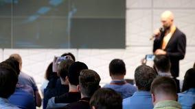 A audiência escuta o conferente vídeos de arquivo