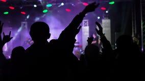 A audiência feliz borrada do fundo video que salta levantando suas mãos areja o grupo rock a audiência do concerto que levanta as filme