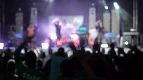 A audiência feliz do fundo video de Blured que salta levantando suas mãos areja o grupo rock a audiência do concerto que levanta  video estoque