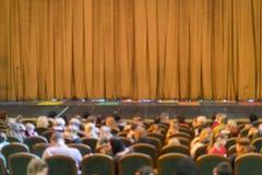Audi?ncia no teatro cortina fechado da fase em um teatro blurry imagens de stock royalty free