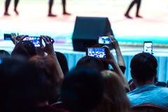 A audiência no tiro do salão alguns dança o desempenho em seus telefones Programa do concerto dos artistas na fase blurry fotos de stock