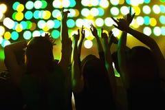 A audiência que olha uma rocha mostrar, as mãos no ar, vista traseira, fase ilumina-se Fotografia de Stock Royalty Free