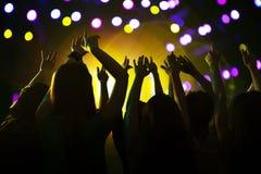 A audiência que olha uma rocha mostrar, as mãos no ar, vista traseira, fase ilumina-se Fotos de Stock