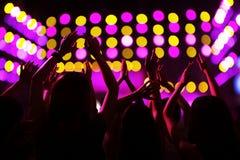 A audiência que olha uma rocha mostrar, as mãos no ar, vista traseira, fase ilumina-se Fotos de Stock Royalty Free