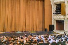 Audi?ncia no teatro cortina fechado da fase em um teatro blurry fotografia de stock
