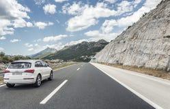 Audi Q5 speeding on the Autobahn among mountain scenery. Stock Photos