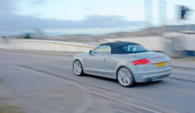 Audi sports car with motion blur. An image of a gray  Audi sports car with soft top. The image is blurred to indicate speed or acceleration Stock Photography