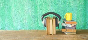 Audia książkowy pojęcie z stertami książki, hełmofony i filiżanka kawy, kopii przestrzeń zdjęcie stock