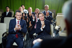 Audience applauding to speaker. Group of male and female business people sitting in conference room, listening attentively to orator and applauding him with Stock Photo