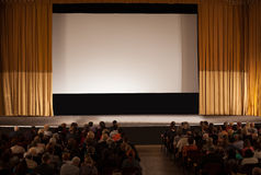 Audience in an auditorium in front of white cinema screen Royalty Free Stock Images
