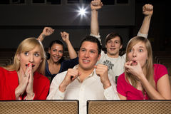 Audience in cinema cheering. Audience in movie theatre cheering and applauding Stock Photos