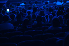 Audience in the cinema. Silhouette. Audience in the cinema. Silhouette shot from back in blue light Stock Photos