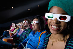 Audience in cinema wearing 3D glasses, smiling, portrait Stock Image