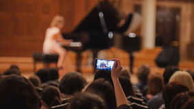 Audience in concert hall during performing piano girl- people shooting performance on smartphone, music opera royalty free stock photos