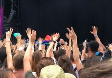 Audience with hands raised at a music festival, empty stage with copy space Stock Images