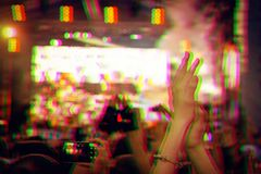 Audience with hands raised at a music festival and lights streaming down from above the stage. Digital signal glitch effect rgb s stock photo