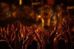 Audience with hands raised at a music festival and lights streaming down from above the stage. Stock Photography