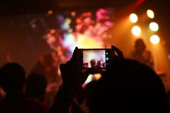 Cellphone mobilephone photographing concert night time. Audience keep taking photo and video at concert with their cellphone focus on the screen with blur Royalty Free Stock Photography