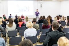 Audience in lecture hall participating at business conference. stock photo