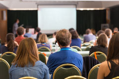 Audience in lecture hall participating at business conference. Royalty Free Stock Images