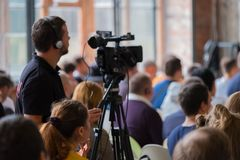 Audience listens to the lecturer. Audience at the conference, camera man broadcasting live video Stock Photo