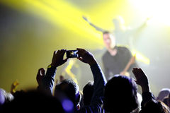 Audience at live concert. Music concert with audience, musicians and man doing a photo Stock Photos