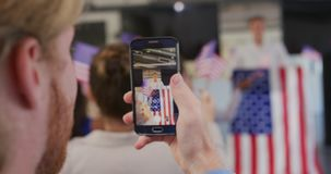 Audience member filming political rally with smartphone
