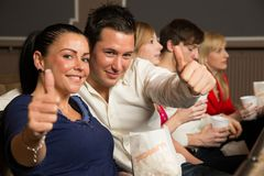 Audience members showing thumbs up Stock Photos