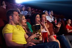 Audience shocked in multiplex movie theater. Audience sitting in multiplex movie theater, watching horror movie, screaming Stock Photo