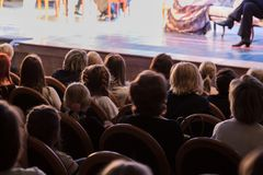 The audience in the theater watching a play. The audience in the hall: adults and children.  Stock Images