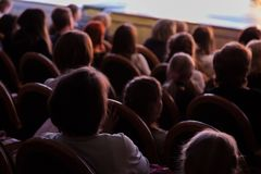The audience in the theater watching a play. The audience in the hall: adults and children.  Stock Photo