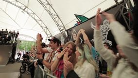 Audience watch at bmx riders in skatepark. Emotions. Applouds. Study cam. stock video