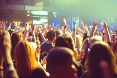 The audience watching the concert on stage. A crowd of spectators at a concert in a small concert club. Applaud and dance near the stage. The audience is filled Stock Photos