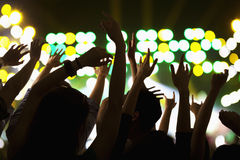 Audience watching a rock show, hands in the air, rear view, stage lights Stock Photo