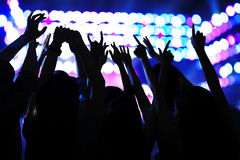 Audience watching a rock show, hands in the air, rear view, stage lights Royalty Free Stock Photos