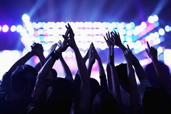 Audience watching a rock show, hands in the air, rear view, stage lights Stock Images