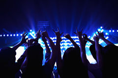 Audience watching a rock show, hands in the air, rear view, stage lights Stock Image