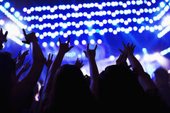 Audience watching a rock show, hands in the air, rear view, stage lights Royalty Free Stock Photo