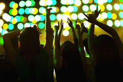 Audience watching a rock show, hands in the air, rear view, stage lights Royalty Free Stock Photography