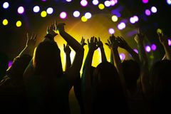 Audience watching a rock show, hands in the air, rear view, stage lights Stock Photos
