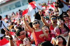 Audience waving Singapore flags during NDP Stock Images
