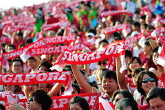 Audience waving Singapore scarves during NDP 2012 Stock Image