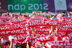 Audience waving Singapore scarves during NDP 2012 Royalty Free Stock Photo