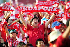 Audience waving Singapore scarves during NDP 2012 Royalty Free Stock Image