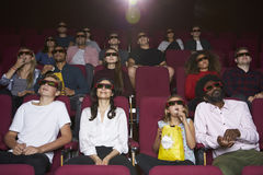 Audiencia en el cine que lleva los vidrios 3D que mira la película Imagen de archivo libre de regalías