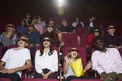 Audiencia en el cine que lleva los vidrios 3D que mira la película de terror Fotos de archivo libres de regalías