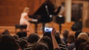 Audiencia en sala de conciertos durante la ejecución de funcionamiento que tira de la gente de la muchacha del piano en el smartp fotos de archivo libres de regalías