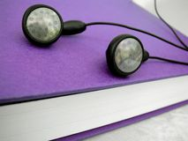 Audio book. Mp3 player ear buds and reading book Stock Photos